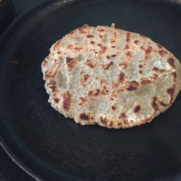 Millet flour roti cooked on a cast iron griddle